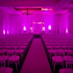 Wedding ceremony with custom chuppah, aisle runner, chivari chairs, uplighting and drape.